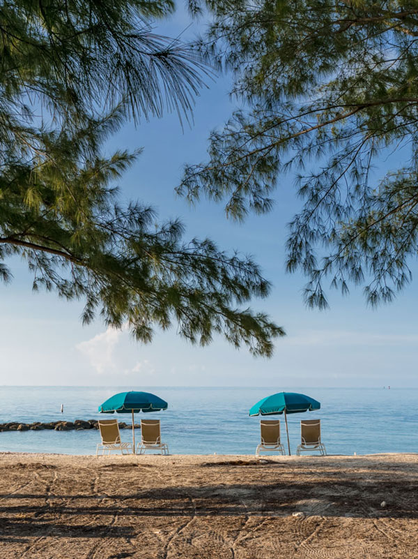 Photo of two beach chair and umbrella set ups on the beach at Fort Zachary Taylor Park.