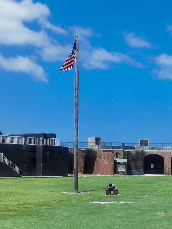 Photo of the American flag and cannon in the middle of the Fort Zachary Taylor courtyard.