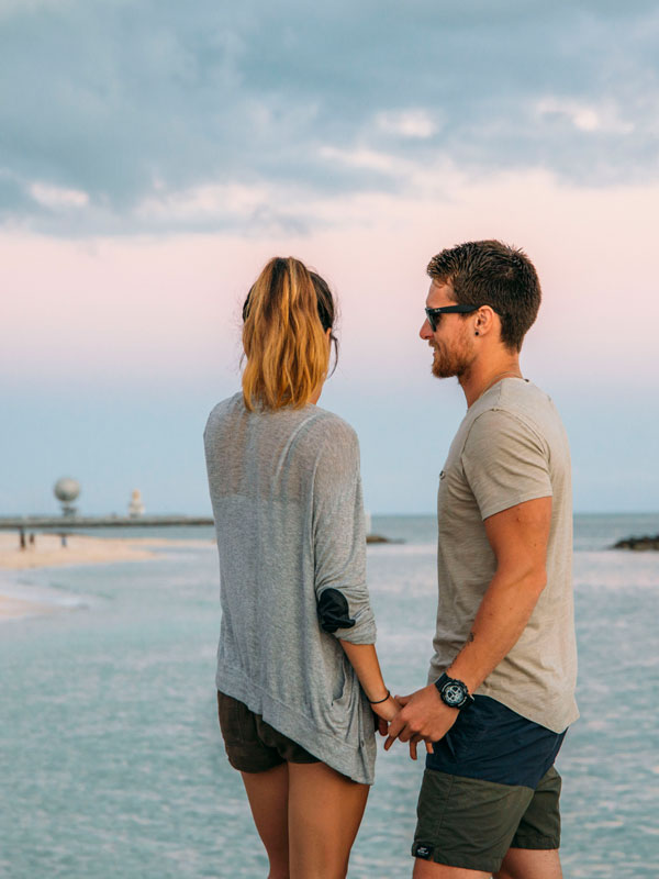 photo of a couple holding hands with the ocean and beach in the background.