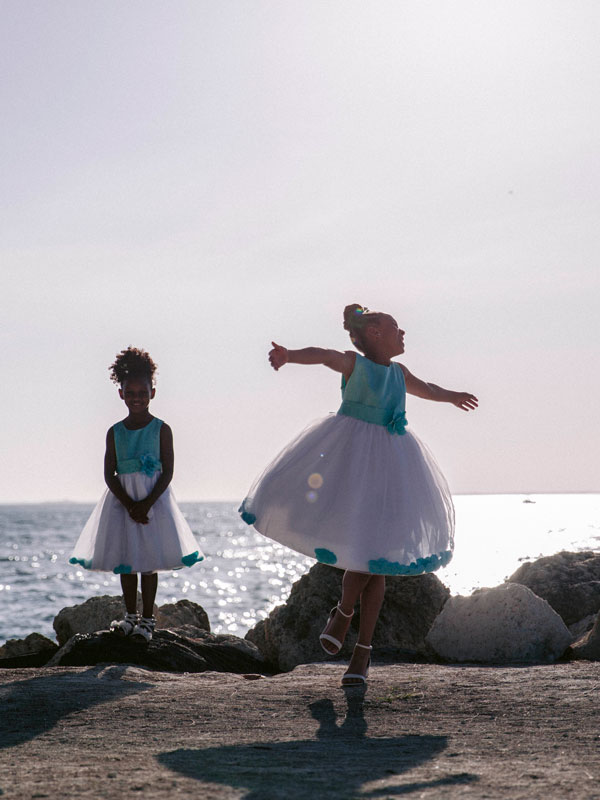 photo of two young girls dancing in dresses at the beach.