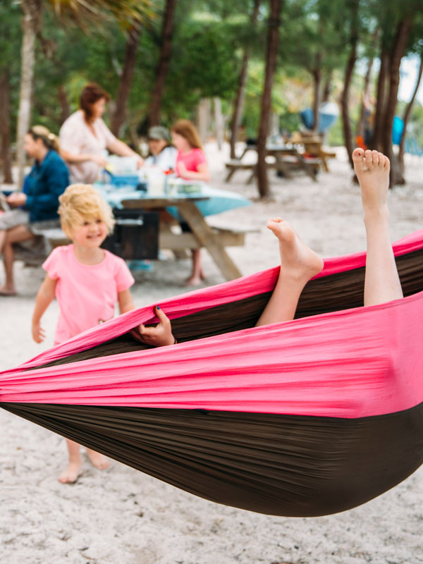 Photo of kids playing in a hammock with feet sticking out.
