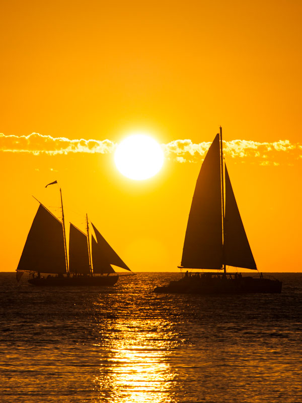 photo of two sailboats on the horizon during a golden sunset.