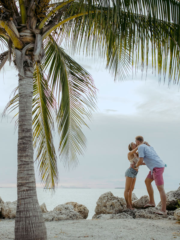photo of a couple kissing under a palm tree.