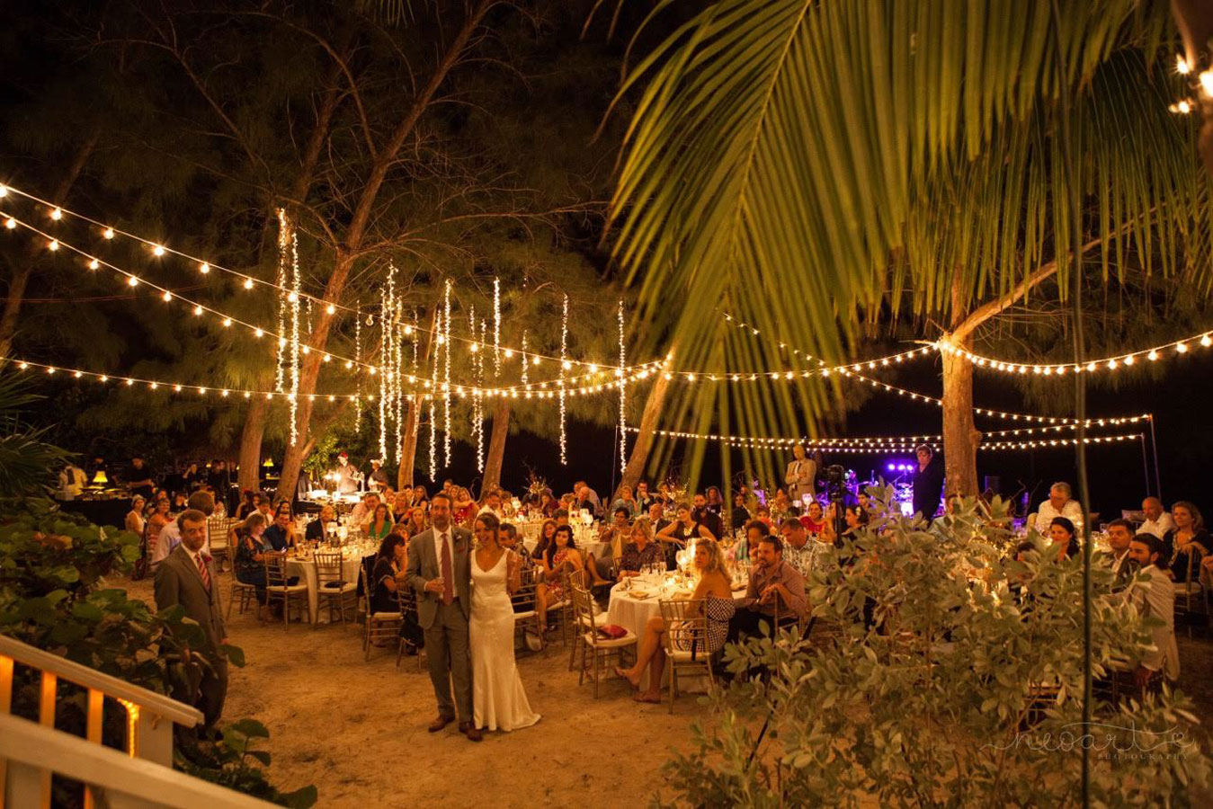 Photo of a wedding reception on a beach at nighttime.